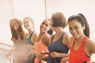 Smiling women holding resistance bands at barre in exercise class gym studioの写真素材 [FYI02702725]