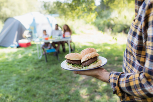 Father serving barbecue hamburgers to family at campsiteの写真素材 [FYI02702730]