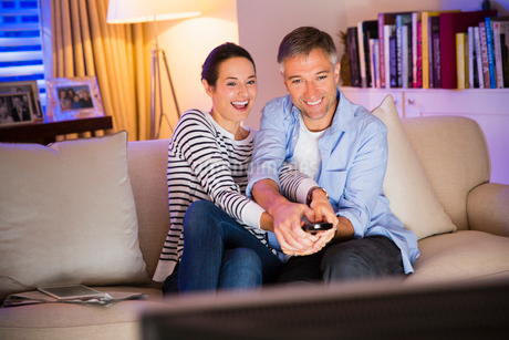 Playful couple fighting over remote control watching TV in living roomの写真素材 [FYI02702783]