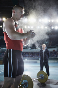 Coach watching male weightlifter applying chalk powder to hands at barbellの写真素材 [FYI02702815]