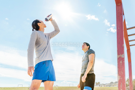 Male runners resting, drinking water at sunny parkの写真素材 [FYI02702861]