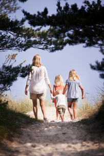 Sweden, Gotland, Faro, Skar, Mother with son (2-3) and daughters (8-9, 10-11) walking along footpathの写真素材 [FYI02702888]