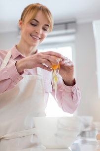 Smiling woman baking, cracking egg over bowl in kitchenの写真素材 [FYI02702941]