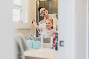 Smiling mother and daughter in bathroom mirrorの写真素材 [FYI02702944]