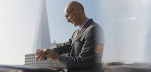 Businessman checking smart watch outdoors, London, UKの写真素材 [FYI02702954]