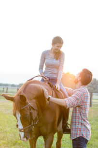Smiling couple horseback riding in rural pastureの写真素材 [FYI02702968]