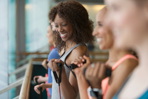 Smiling women using resistance bands in exercise class gym studioの写真素材 [FYI02702979]