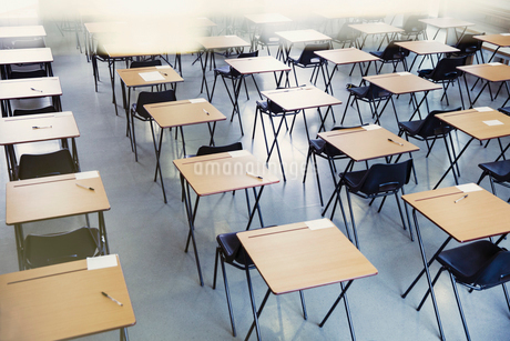 Pens and index cards on desks in empty classroomの写真素材 [FYI02703042]