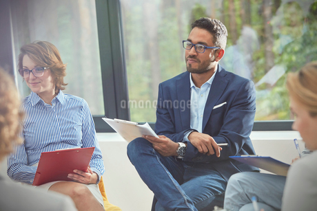Attentive man with clipboard listening in group therapy sessionの写真素材 [FYI02703101]