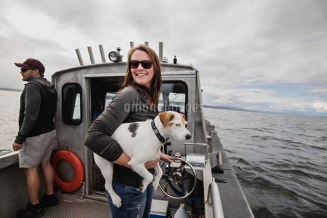 Portrait smiling woman with dog on fishing boatの写真素材 [FYI02703133]