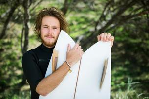 Australia, Queensland, Sunshine Coast, Noosa, Alexandria Bay, Portrait of young man holding surfboarの写真素材 [FYI02703135]