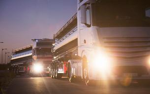 Stainless steel milk tankers in queue at nightの写真素材 [FYI02703136]