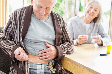 Older man giving himself injectionの写真素材 [FYI02703153]