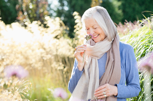 Older woman smelling flowers outdoorsの写真素材 [FYI02703176]