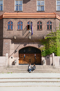 Sweden, Stockholm, Ostermalm, Students sitting on stairs in front of school buildingの写真素材 [FYI02703252]