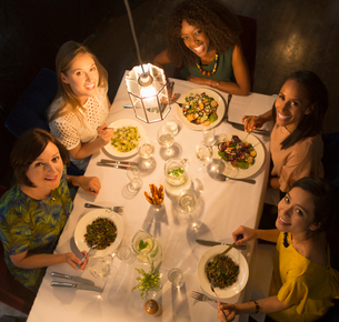 Portrait smiling women friends dining at restaurant tableの写真素材 [FYI02703254]