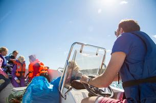 Sweden, Swedish West Coast, Halland, Kungsbackafjorden, Man with kids (6-7, 8-9, 10-11) on motor boaの写真素材 [FYI02703285]