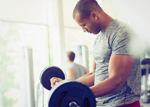 Focused man doing barbell biceps curls at gymの写真素材 [FYI02703373]