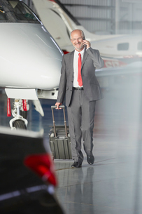 Smiling businessman pulling suitcase talking on cell phone in airplane hangarの写真素材 [FYI02703400]