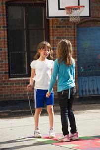 Sweden, Uppland, Norrmalm, Two girls (8-9) playing in schoolyardの写真素材 [FYI02703438]