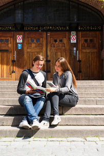 Sweden, Stockholm, Ostermalm, Students sitting on stairs in front of school buildingの写真素材 [FYI02703456]