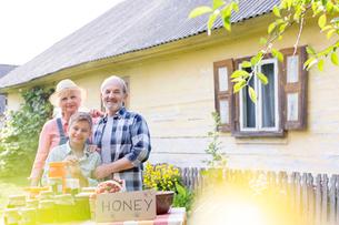 Portrait proud grandparents and grandson selling honeyの写真素材 [FYI02703462]