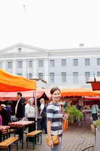 Finland, Uusimaa, Helsinki, Kauppatori, Smiling woman holding carrot at street marketの写真素材 [FYI02703534]