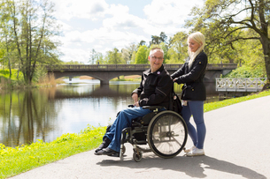 Sweden, Ostergotland, Mjolby, Man on wheelchair with personal assistant in parkの写真素材 [FYI02703605]