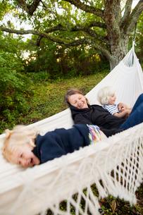 Sweden, Gotland, Havdhem, Grandmother and grandchildren (2-3, 4-5) in hammockの写真素材 [FYI02703625]