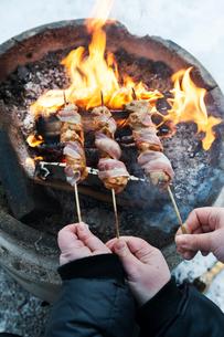 Sweden, Stockholm, Bjorkhagen, Hammarbybacken, People cooking bacon wrapped chicken kebabs on flameの写真素材 [FYI02703629]