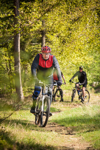 Sweden, Blekinge, Solvesborg, Ryssberget, Mature men riding on mountain bikes through forestの写真素材 [FYI02703672]