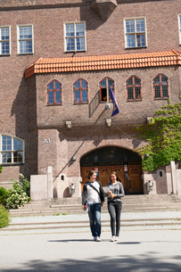 Sweden, Stockholm, Ostermalm, Students walking in front of school buildingの写真素材 [FYI02703694]