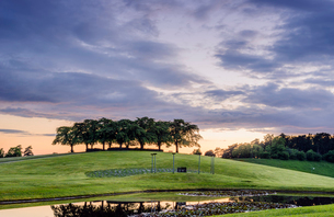 Sweden, Sodermanland, Stockholm, Gamla Enskede, Skogskyrkogarden, Green landscape with pond at sunseの写真素材 [FYI02703723]
