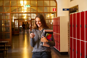 Sweden, Stockholm, Ostermalm, Female student texting on mobile phoneの写真素材 [FYI02703747]