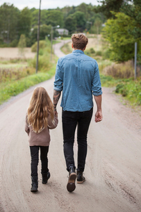 Finland, Uusimaa, Raasepori, Karjaa, Father walking with daughter (6-7) along country roadの写真素材 [FYI02703748]