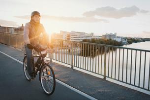 Sweden, Sodermanland, Stockholm, Hornstull, Liljeholmsbron, Man riding bike on bridge at sunsetの写真素材 [FYI02703755]