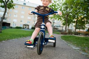 Sweden, Vastergotland, Mullsjo, Boy (4-5) riding tricycleの写真素材 [FYI02703769]