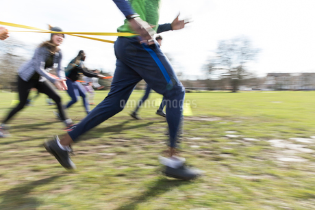 People racing, doing team building exercise in sunny parkの写真素材 [FYI02703789]