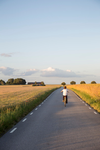 Sweden, Skane, Soderslatt, Beddinge, Boy (12-13) riding bicycle on country roadの写真素材 [FYI02703812]