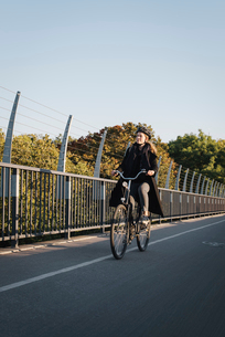 Sweden, Sodermanland, Stockholm, Vasterbron, Young woman riding bikeの写真素材 [FYI02703822]