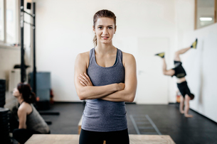 Germany, Portrait of young woman standing in gym with arms crossedの写真素材 [FYI02703838]