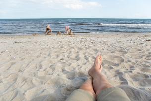 Sweden, Skane, Soderslatt, Beddinge, Father with daughter (10-11) and son (12-13) on beachの写真素材 [FYI02703844]