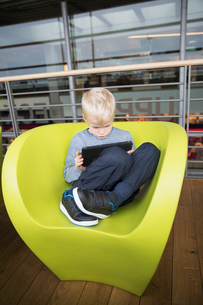 Germany, Hamburg, Boy (6-7) sitting at airport hall and using tabletの写真素材 [FYI02703856]
