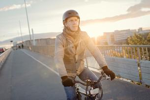 Sweden, Sodermanland, Stockholm, Hornstull, Liljeholmsbron, Man riding bike on bridge at sunsetの写真素材 [FYI02703880]