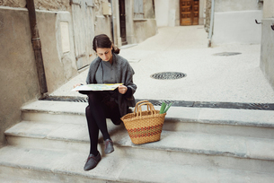 France, Languedoc-Roussillon, Sauve, Young tourist sitting on steps and looking at mapの写真素材 [FYI02703899]