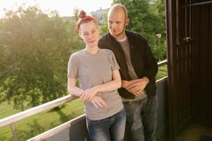 Sweden, Vasterbotten, Norrmjole, Young couple standing on balconyの写真素材 [FYI02703900]
