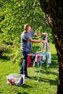 Finland, Paijat-Hame, Heinola, Man hanging laundry on drying rackの写真素材 [FYI02703917]