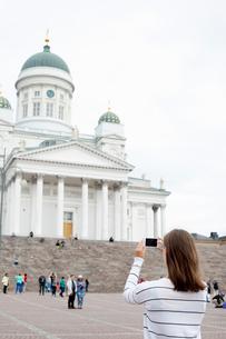 Finland, Uusimaa, Helsinki, Senaatintori, Young woman photographing Lutheran Cathedralの写真素材 [FYI02703943]