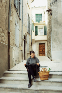 France, Languedoc-Roussillon, Sauve, Young tourist sitting on steps and looking at mapの写真素材 [FYI02703965]