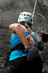 Sweden, Ostergotland, Vaderstad, Rear view of woman climbing rockの写真素材 [FYI02703975]